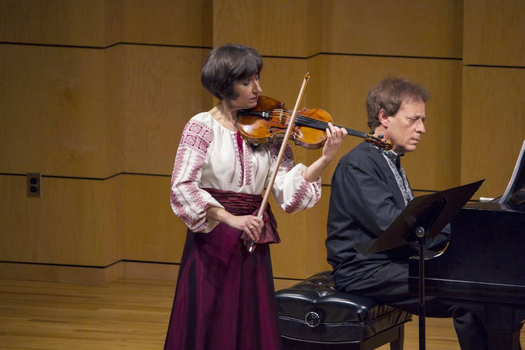 Woman playing a violin next to a man who is playing piano
