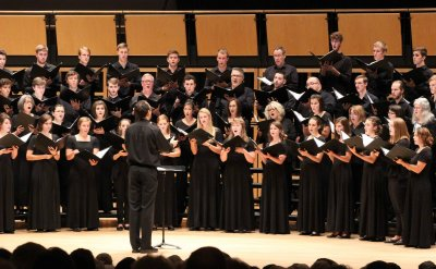 Group of people of all ages singing in a choir on stage