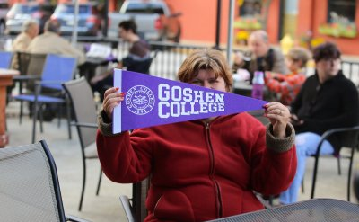 Woman holding Goshen College flag with sitting at an outside table