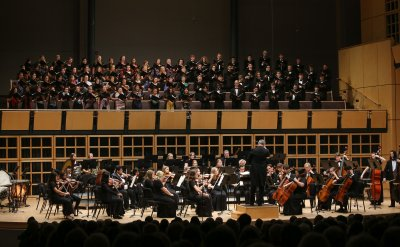 Choir singing with full orchestra on stage