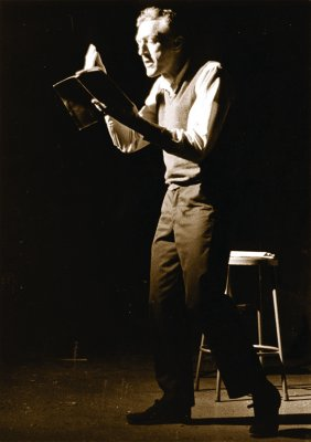 Sepia photo of a man standing and reading with a stool behind him