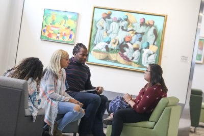 Four alumni gather in the Hunsberger Commons during Homecoming Weekend, gathered in front of two pieces of Haitian artwork that depict the Haitian people.