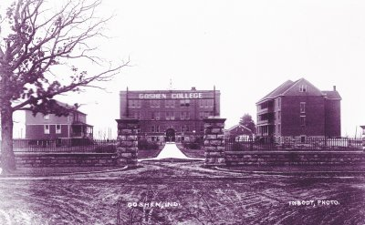 Purple photo of three buildings with a stone fence surrounding them