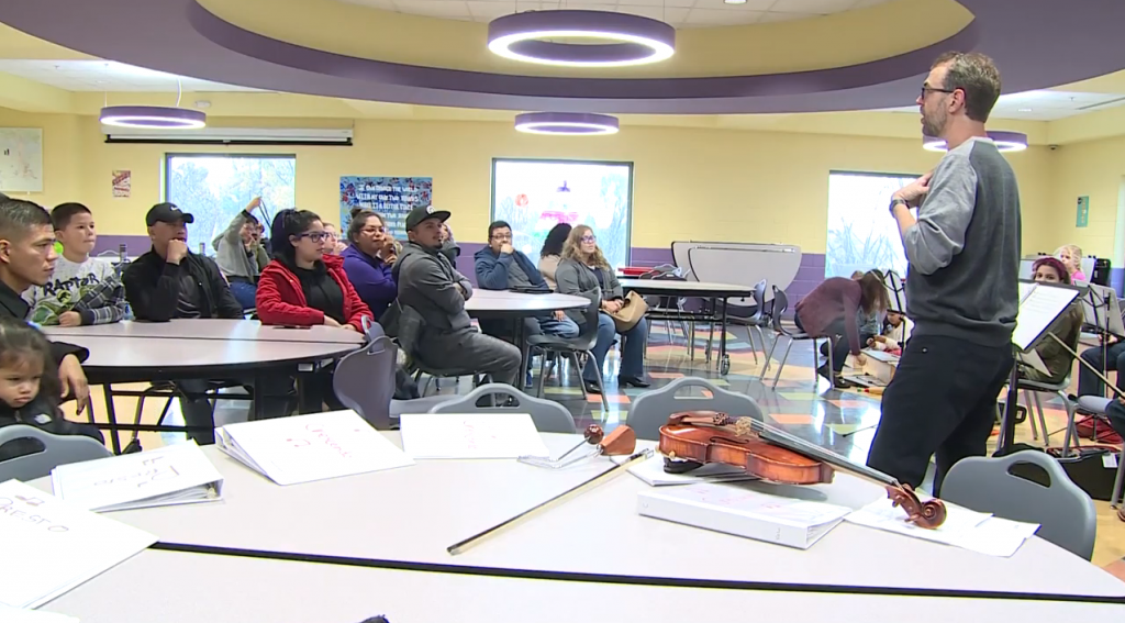 A man teaching a classroom full of students with a violin next to him