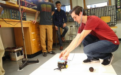 Three students, with one student working on a small wheeled robot