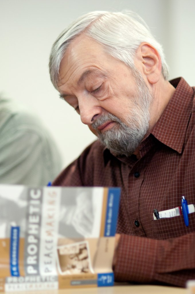 Man reading a book called 'Prophetic Peace Making'