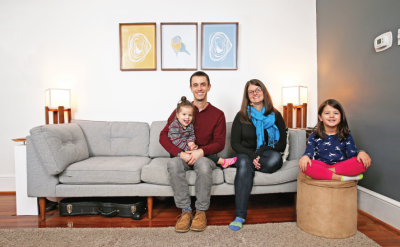 A man and a woman sitting together on a couch with two young girls