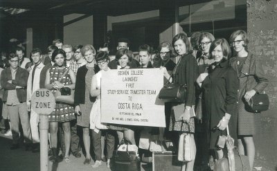 A black and white image of a group of college students in 1968, holding up a sign that reads