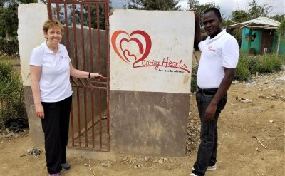 A man and a woman standing in front of a sign 'Caring Hearts for Central Haiti'