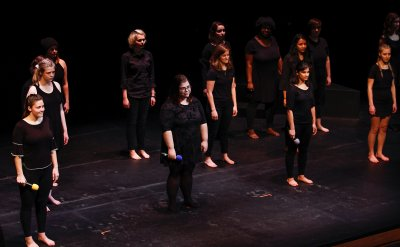 A group of women standing on a stage barefoot wearing black