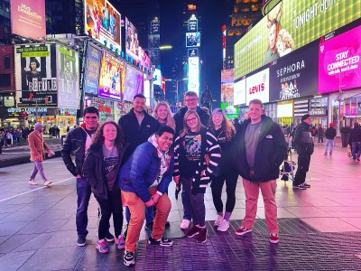 Group of people posing for a photo with lots of glowing advertisements and lights around them