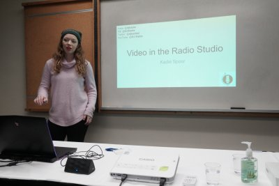 "Woman giving a powerpoint presentation. ""Video in the Radio Studio'"