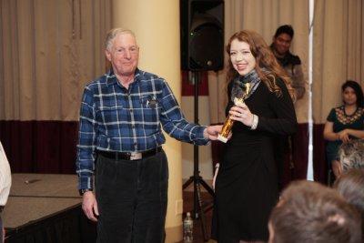 Woman receiving an award from an older man