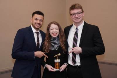 Two men posing for a photo with a woman who is holding an award