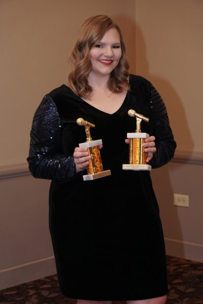 Woman holding two awards