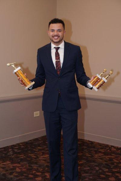 Man holding three awards
