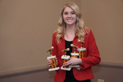Woman holding four awards