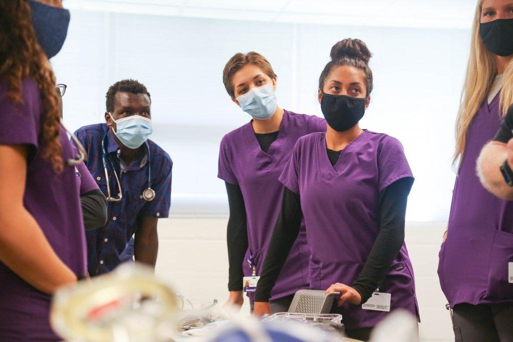 Three nursing students wearing purple scrubs and masks look off-camera