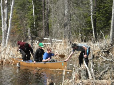 Logan Miller pulls Daniel Graber, Rebekah Steiner, and Sunday Mahaja across a submerged portion of a portage trail leading to Shell Lake.